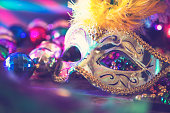Mardi Gras or Rio Carnival mask and colorful carnival decorations.  Scene includes: gold feathered mask, colored party lights, and beads.  Objects lie on wooden table.  No people.