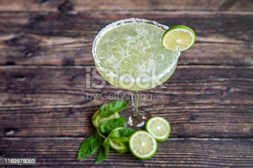 Margarita cocktail  with lemon slices and mint leaf.