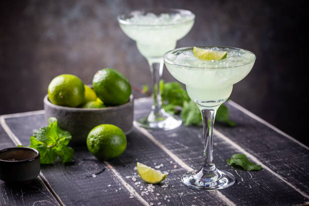 margarita cocktail with lime margarita cocktail with lime in a glass on dark background garnish stock pictures, royalty-free photos & images