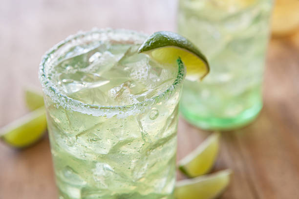 Margaritas Close up Margarita, outside on a wood table with margarita and tequila in background, selective focus margarita stock pictures, royalty-free photos & images
