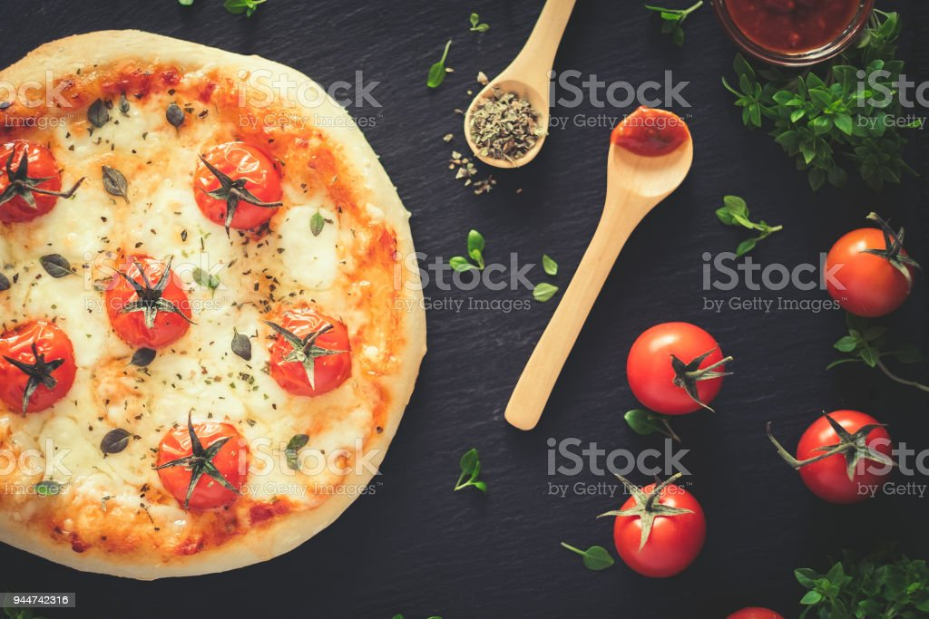 Margherita home made pizza. Top view on dark table stock photo