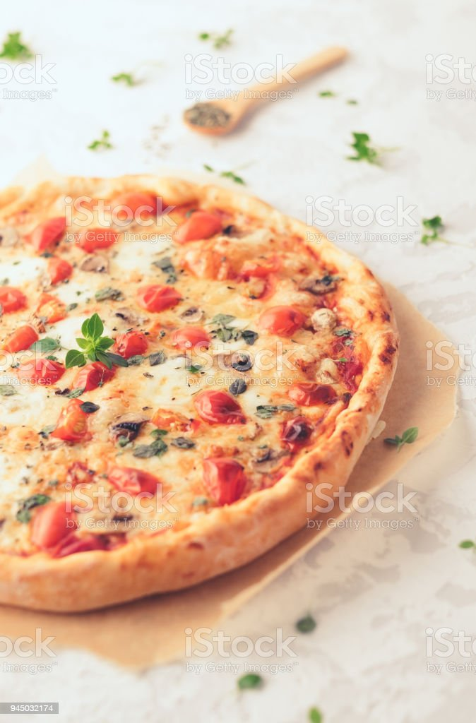 Margherita home made pizza with mushrooms on white table stock photo