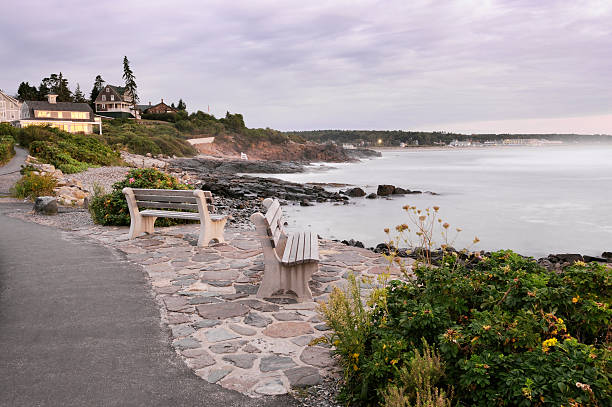Marginal way Asphalt trail called marginal way along the coastline of Ogunquit in Maine (United States) where you can relax on bench for scenic view at sunrise.  Best of Maine and New England in lightbox below... rocky coastline stock pictures, royalty-free photos & images
