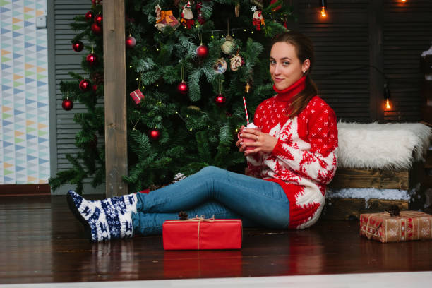 Marhsmallow and gifts with beautiful girl near christmas tree. stock photo