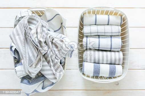 istock Marie Kondo tidying concept - folded kitchen linens in white basket 1164403347