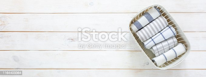 istock Marie Kondo tidying concept - folded kitchen linens in white basket 1164403364