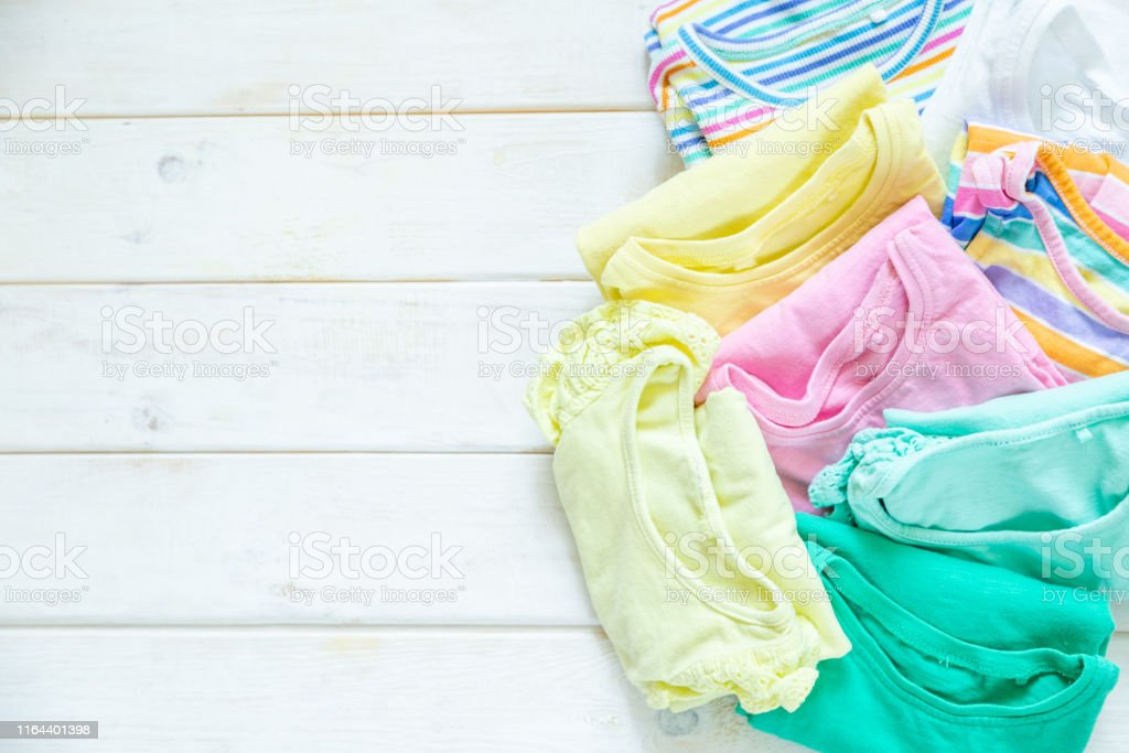 Marie Kondo tyding up method concept - folded kids clothes in pastel...