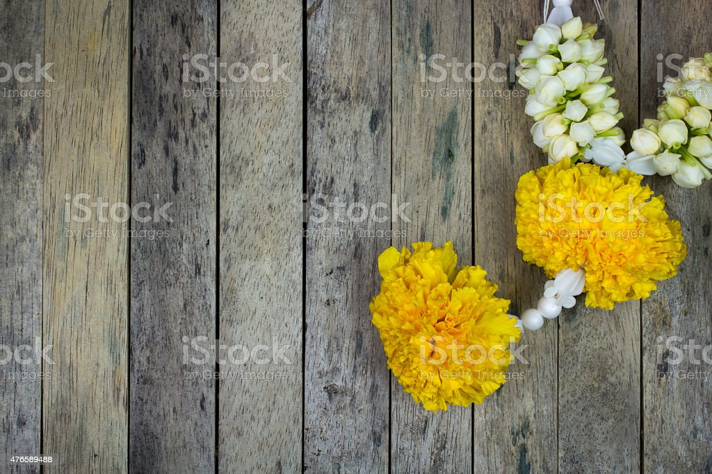 marigold flower garland on wood plank, top view stock photo