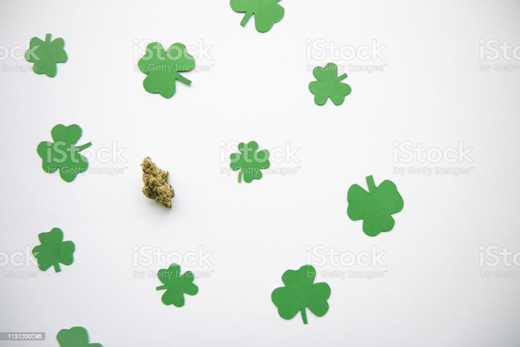 Marijuana Bud against Four and Three Leaf Clovers St Patricks St Pattys Day - Top Down, Left Aligned View stock photo
