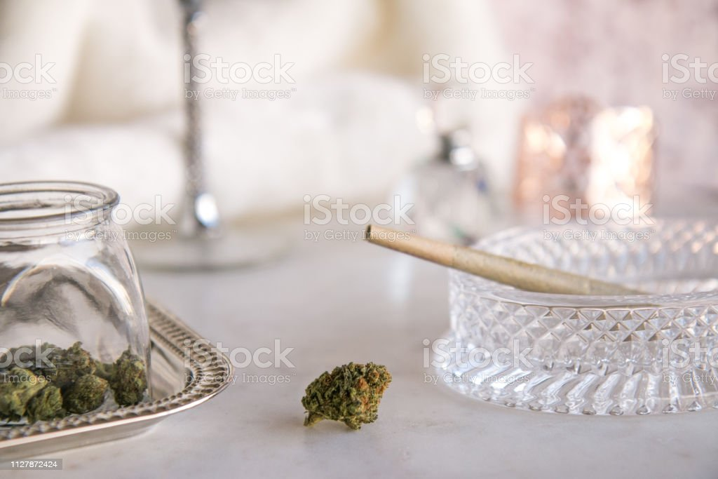 Marijuana Bud on Marble Vanity with Joint in Crystal Ashtray and Cannabis Jar Luxury Cannabis stock photo