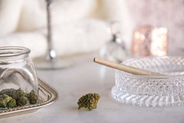 Marijuana Bud on Marble Vanity with Joint in Crystal Ashtray and Cannabis Jar Luxury Cannabis stock photo
