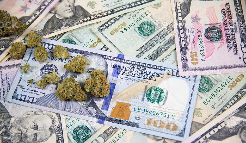 Marijuana bud on top of United States cash money royalty-free stock photo
