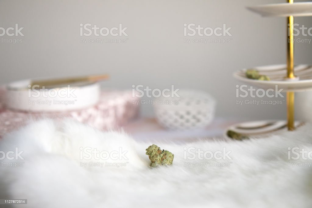 Marijuana Bud on White Fur with Joint in Background Vanity Luxury Cannabis stock photo