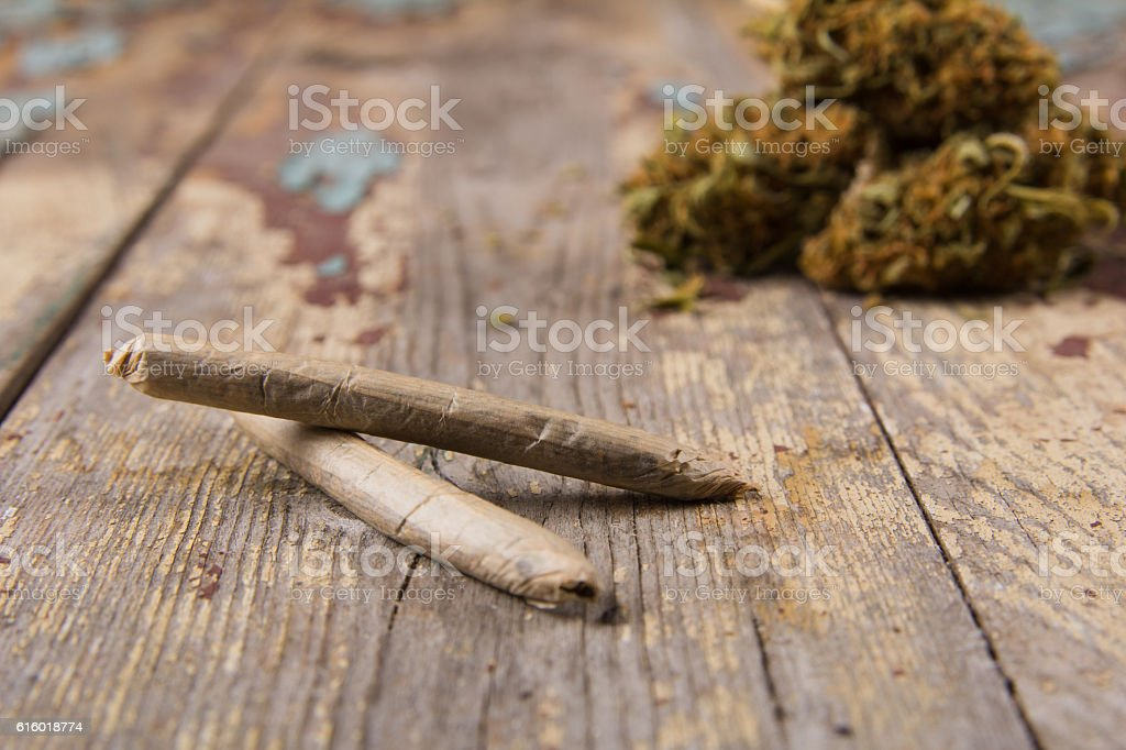 Marijuana buds and joints on the rustic wooden table stock photo