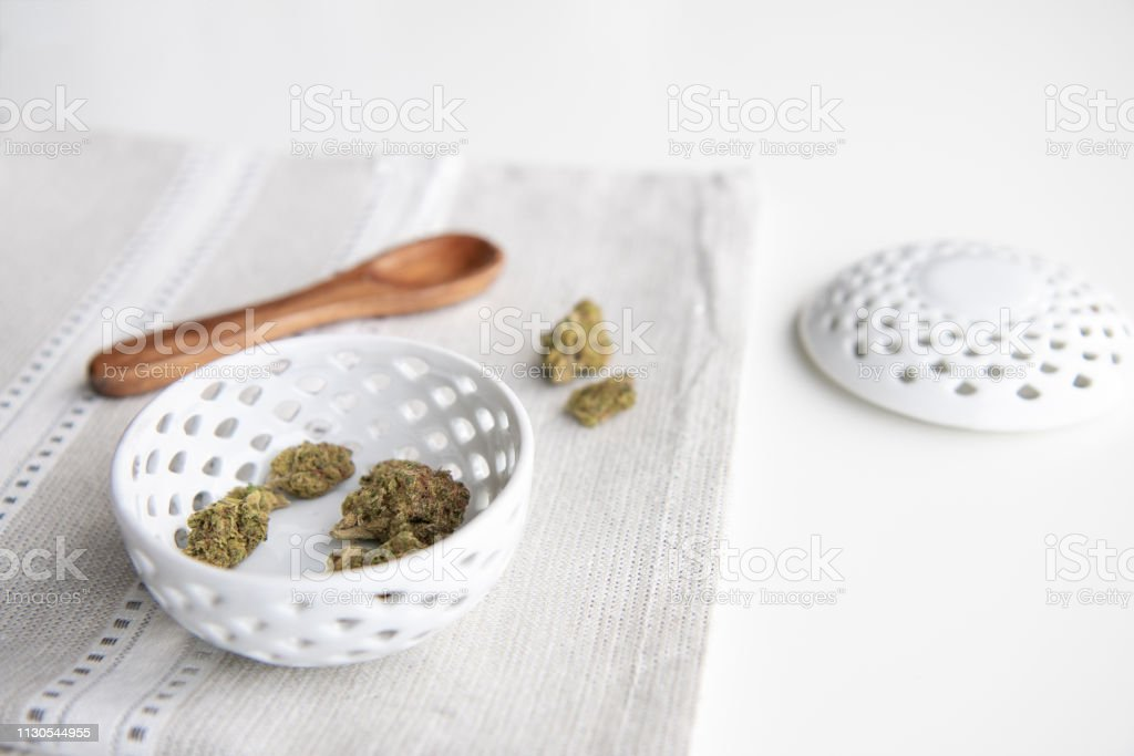 Marijuana Buds in a Porcelain Bowl on a Silver Placemat with Wooden Spoon and Lid - Minimalist Cannabis stock photo
