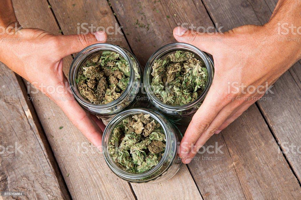 Marijuana buds in glass jars stock photo