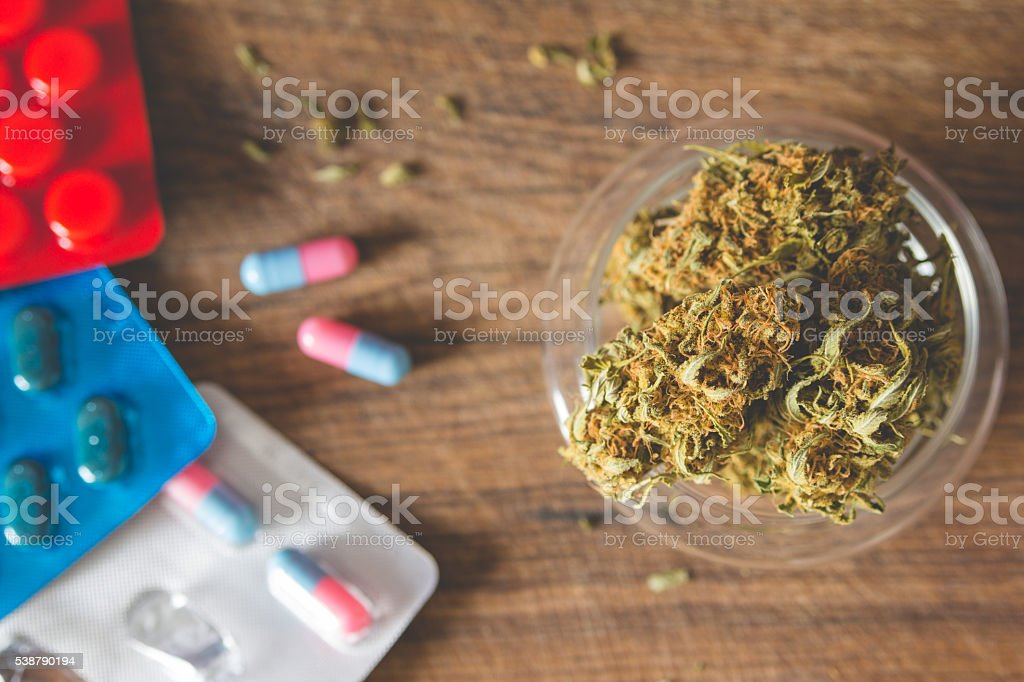 Marijuana buds in the glass plate and medications stock photo