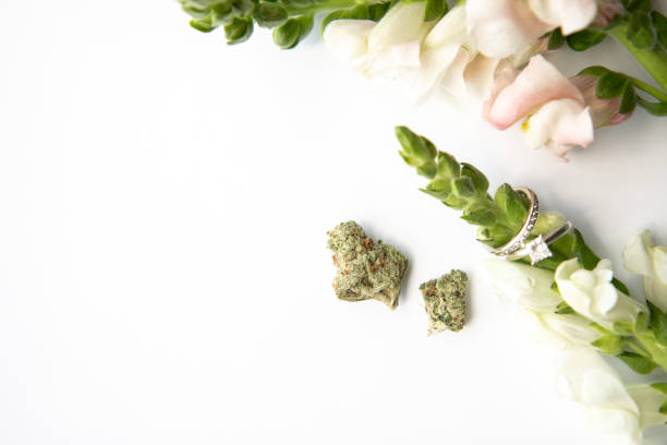 Marijuana Buds next to Diamond Wedding and Engagement Ring Around Flowers - Cannabis Wedding stock photo