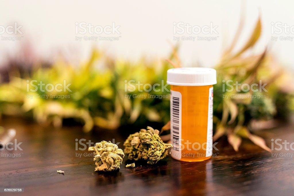 Marijuana buds sitting next to prescription medicine bottle stock photo