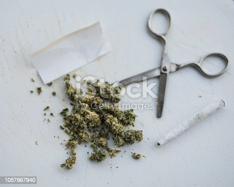 istock Marijuana buds with scissors and rolling paper, along with an already rolled joint. 1057667940