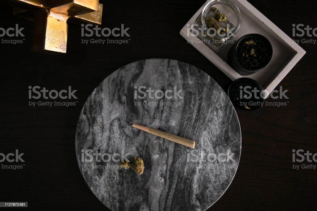 Marijuana Joint and Buds Top Down on Dark Marble Luxury Cannabis stock photo