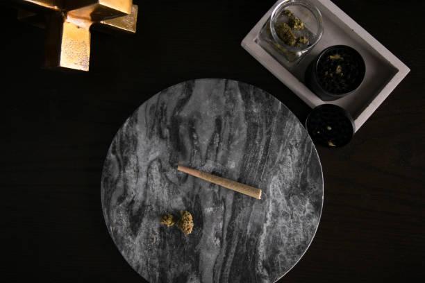 Marijuana Joint and Buds Top Down on Dark Marble Luxury Cannabis stock photo
