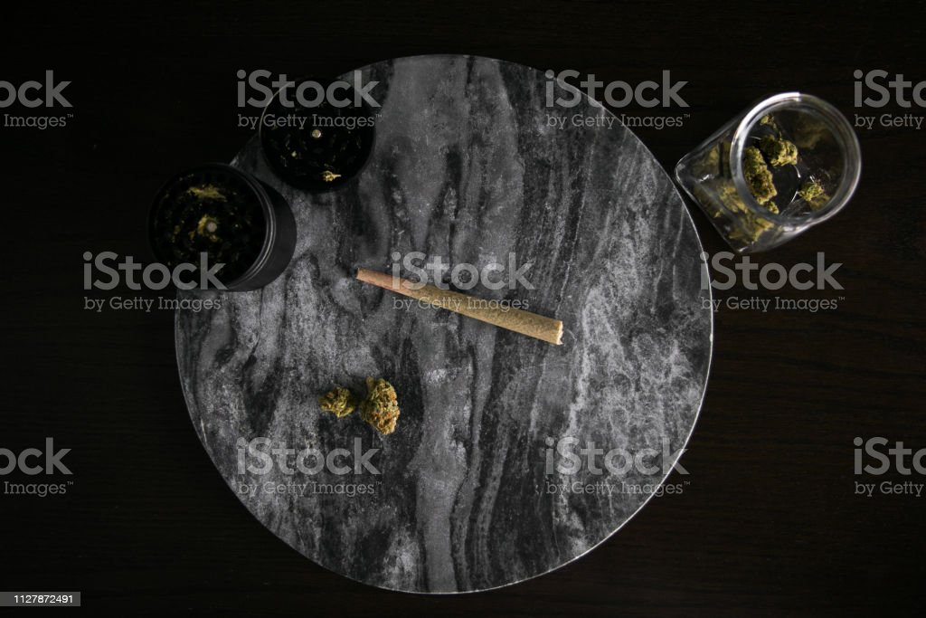 Marijuana Joint, Buds and Grinder (left) Top Down on Dark Marble Luxury Cannabis stock photo