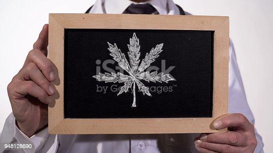 istock Marijuana leaf drawn on blackboard in therapist hands, cannabis legalization 948128690