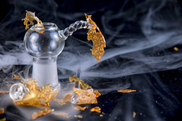 Marijuana oil concentrate aka shatter isolated with glass rig on black background stock photo