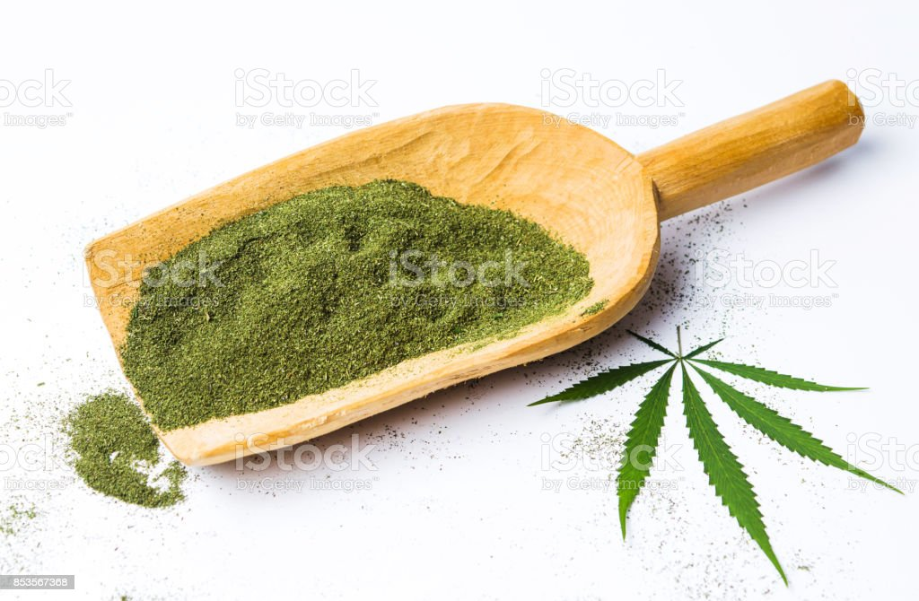Marijuana powder in a big wooden spoon isolated stock photo