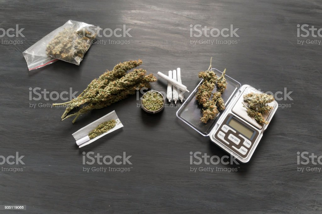 Marijuana, scales, jambs and a cannabis grinder on a black woode The concept of marijuana legalization and the use of cannabis for medical purposes stock photo