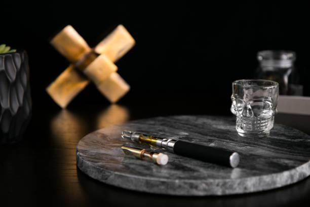 Marijuana Vape Pen and Concentrate on Dark Marble Luxury Cannabis stock photo