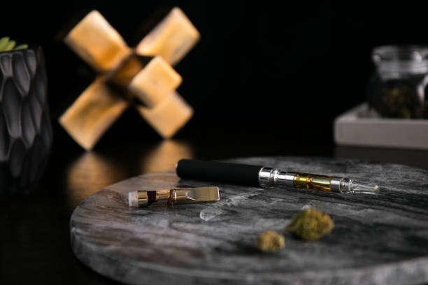 Marijuana Vape Pen, Concentrate and Buds Close Up on Dark Marble Luxury Cannabis stock photo