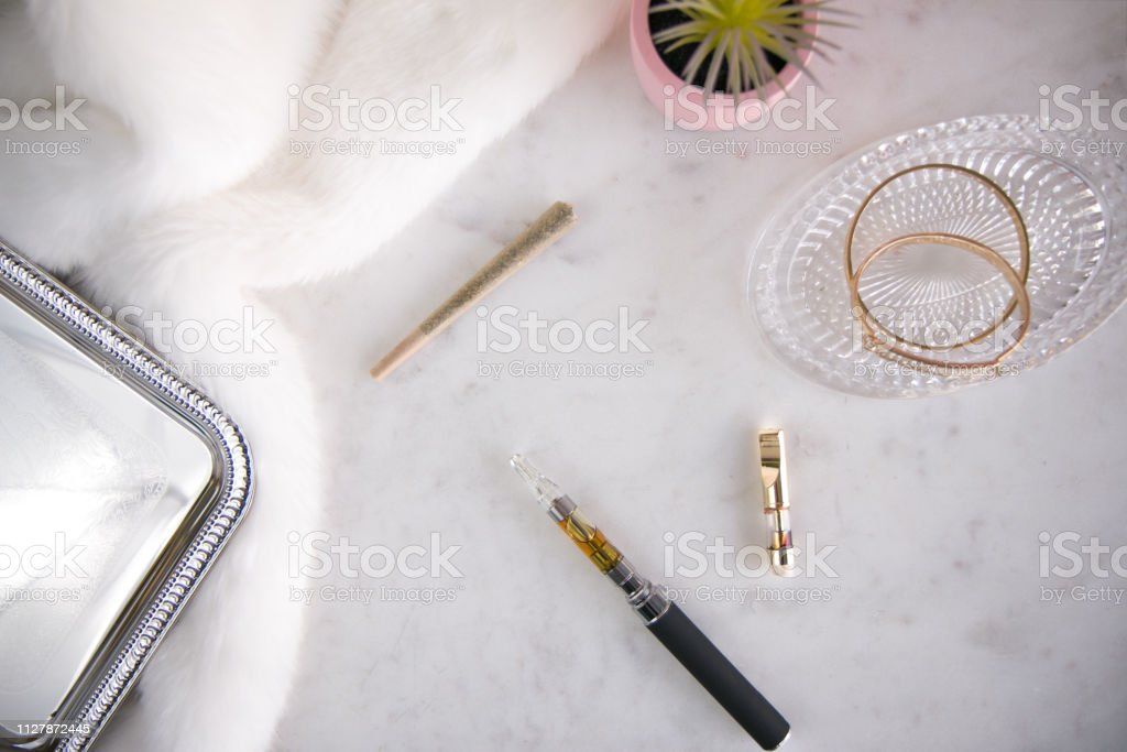 Marijuana Vape Pen with Concentrate and Joint on White Marble Top Down Luxury Cannabis stock photo