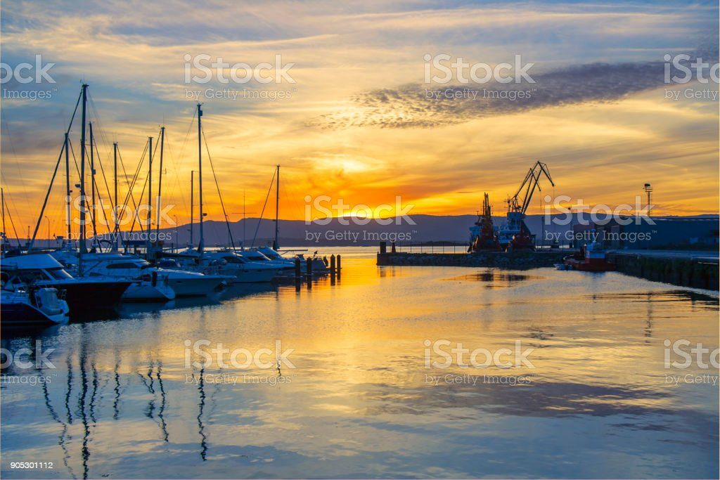 Marina and commercial harbor at sunset stock photo
