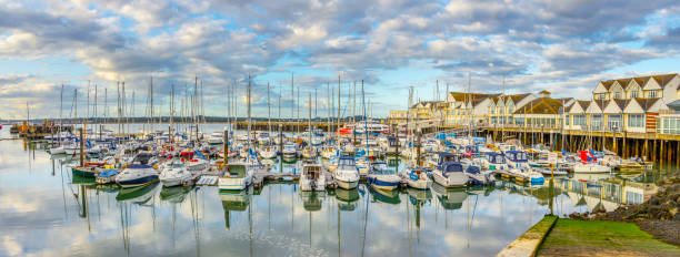 Marina and harbor in Southampton, UK, with tranquil waters reflecting clouds, sky. stock photo