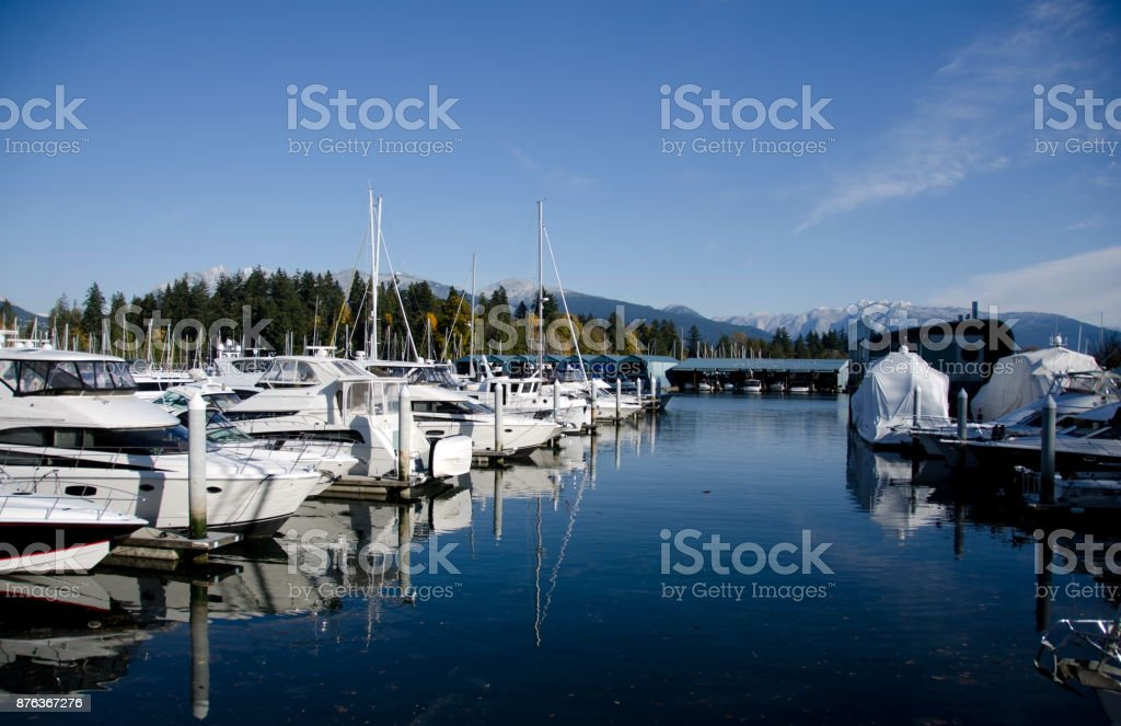 Marina at Coal harbor on a sunny morning with view of Grouse mountain, Vancouver stock photo