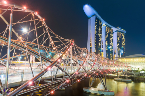 Singapore , Singapore - November 3, 2012: Marina Bay Sands Hotel and the Double Helix Bridge in Singapore at night. Tourists passing over the bridge. Marina Bay Sands is an integrated resort fronting Marina Bay in Singapore.