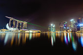 A long exposure, wide angle, panorama at night of the Marina Bay, in Singapore, showing a beautiful show of laser and neon lights show.