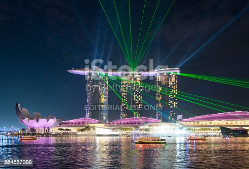 Singapore, Singapore - April 15, 2016: Night view of the Marina Bay Sands Hotel in the centre. The ArtScience Museum in Singapore is showing to the left. On top of the Marina Bay sands Hotel a laser light show is running.