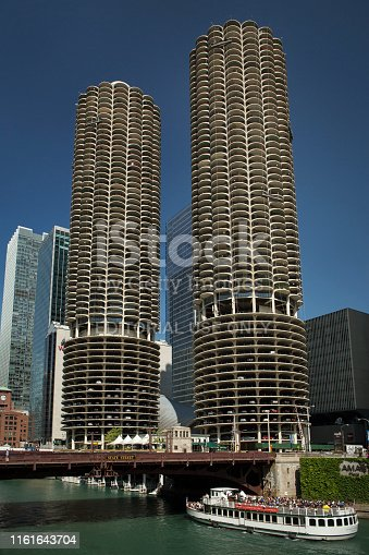 Chicago, Illinois: Vertical frontal view of the Marina City towers by the Chicago River with a tourist cruise sailing under the State St Bridge on a sunny day
