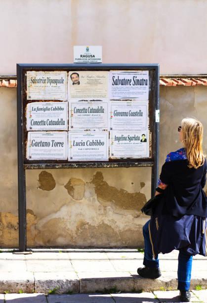 marina di ragusa, sicilien: kvinna läser gemenskapen dödsannonser - italy poster bildbanksfoton och bilder