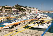 Cala Ratjada, Majorca, Spain - August 22, 2012: Daytime view of marina and promenade under clear blue sky.