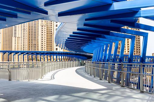 Dubai, UAE, 22.02.2021. Marina Pedestrian Bridge footbridge at the intersection of King Abdullah Bin Abdulaziz Al Saud Street and Al Gharbi Street, modern urban architecture with geometric structures.
