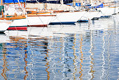 Yachts masts reflected in the water of Marseille's  Vieux Port (Old Harbour) in France.
