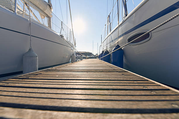 Marina with anchored boats Perspective of small floating pier on still water mooring stock pictures, royalty-free photos & images