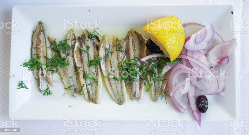 Marinated anchovies on a white plate. stock photo
