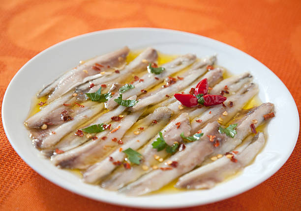 Marinated anchovies Anchovies marinated in lemon with hot pepper and parsley anchovy stock pictures, royalty-free photos & images