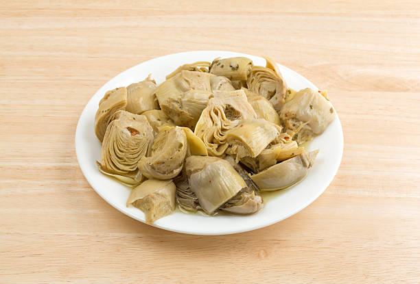 Marinated artichoke hearts on a plate atop a table - foto stock