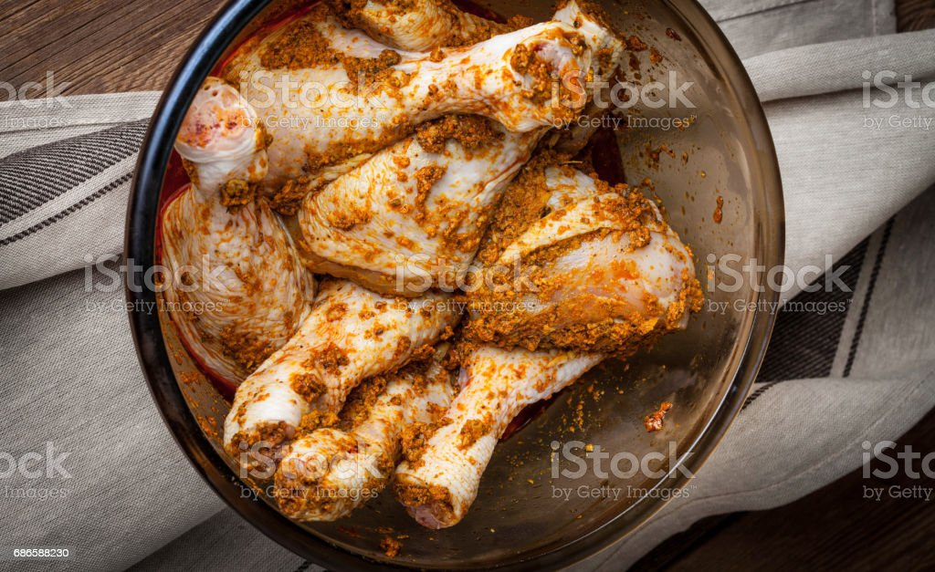 Marinated chicken drumsticks in a glass bowl. royalty-free stock photo